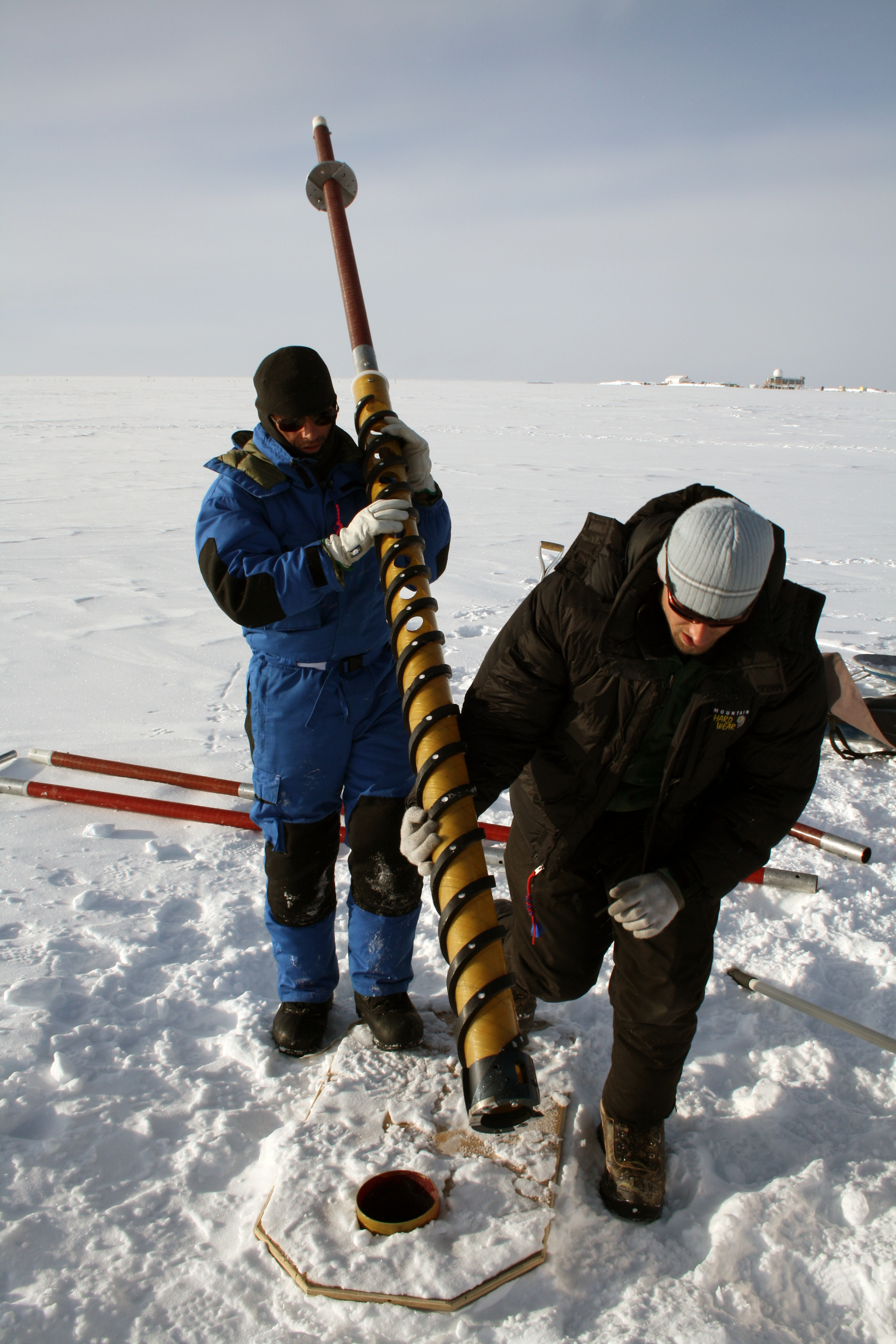 A scientist operates a hand auger outside of Summit Station, Greenland