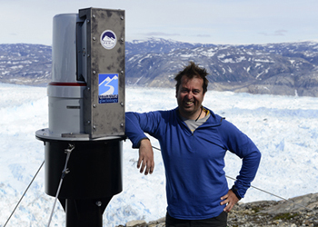 Gordon Hamilton with an automated laser scanning system installed to monitor Helheim Glacier, in Southeast Greenland