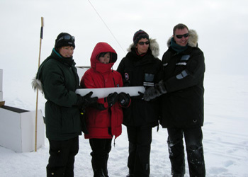 People holding an ice core at Summit, Greenland