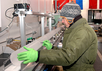 Science technician Tommy Cox measures a section of the WAIS Divide ice core as it begins its journey down the core processing line at the National Ice Core Laboratory near Denver