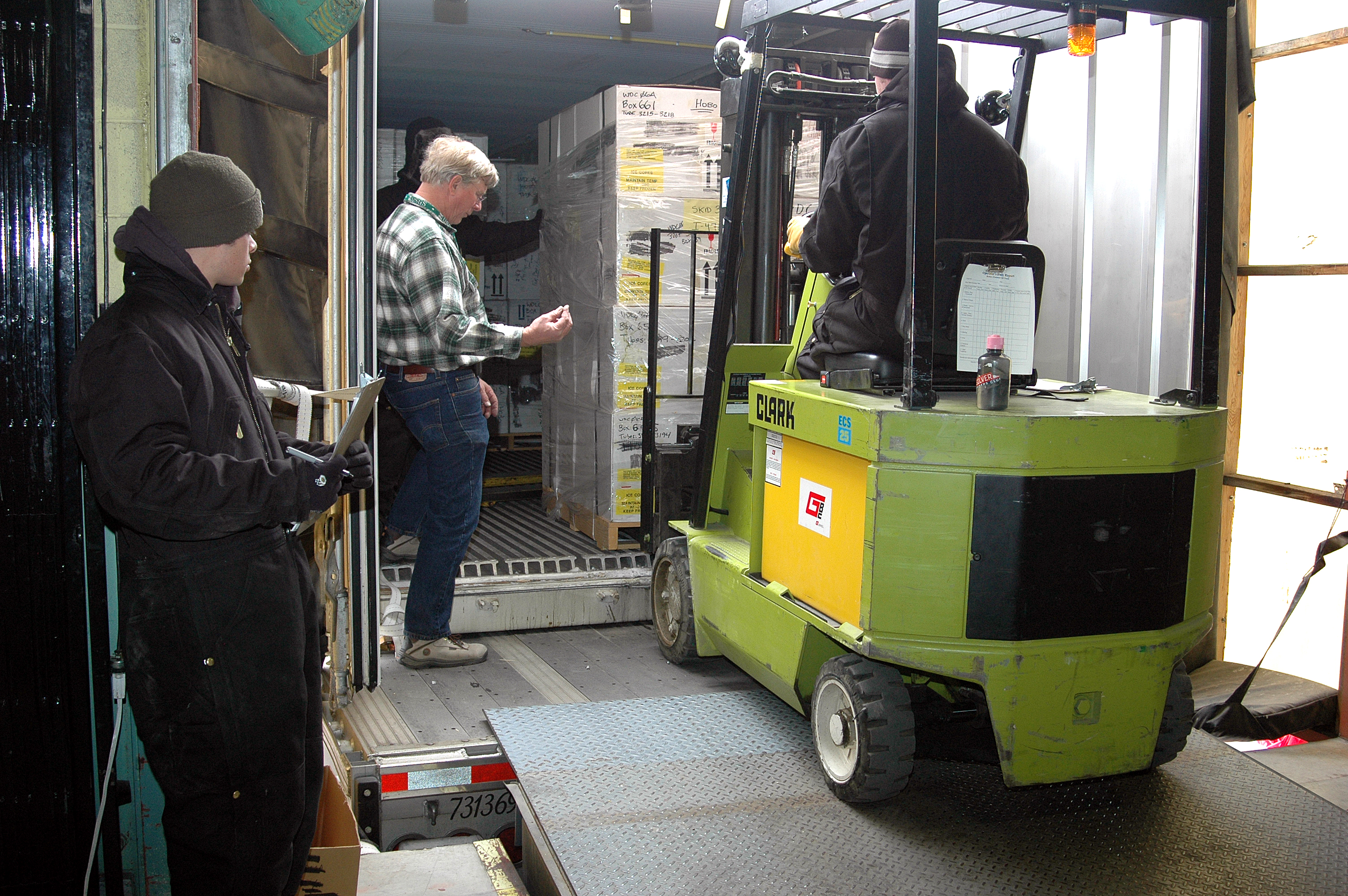 A forklft moves a pallet of ice cores in boxes