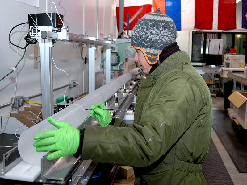 A science technician measures a section of the WAIS Divide ice core as it begins its journey down a core processing line
